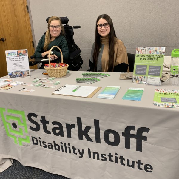 Sarah Schwegel and Katie Fields sit at a table with Starkloff Disability Institute's logo displayed on the table cloth.