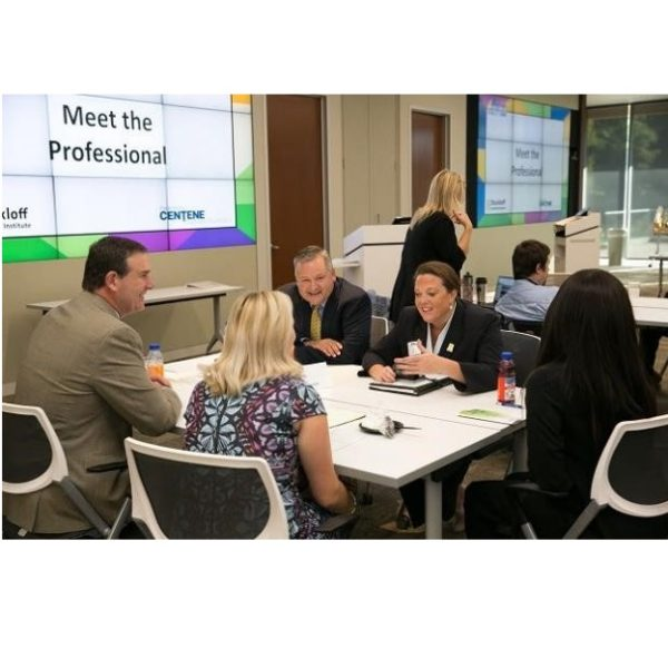 Image of five people in business attire chatting around a table.