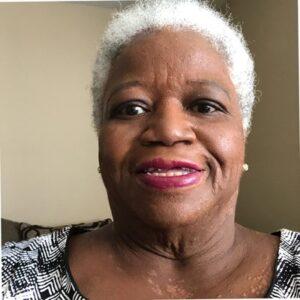 Barbara Labinjo is smiling. Barbara has brown skin, white short hair and is wearing red lipstick.