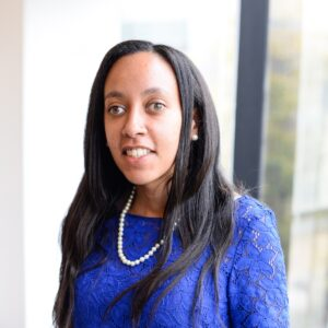 Haben Girma is smiling at the camera. Haben has light brown skin, long straight hair parted to the side, and is wearing a blue eyelet shirt.