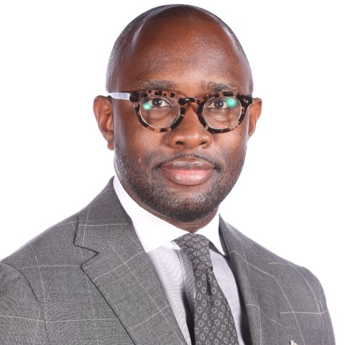 Wale Soluade looks directly at the camera. Wale has deep brow skin, a shaved head and wears rounded tortoise shell glasses. He is wearing a grey suit and a grey tie.