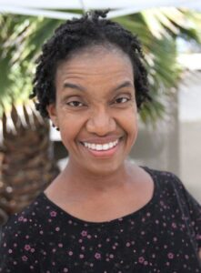 Diana Elizabeth Jordan is smiling. Diana has medium brown skin, has small locs and is wearing a black shirt with patterns.