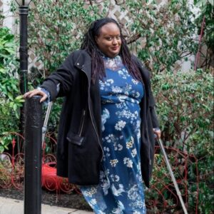 Imani Barbarin is posing outside with her crutches, Imani has brown skin, hair in chest-length locs and is wearing a blue floral dress and a black jacket.