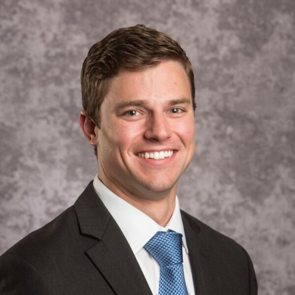 Kevin Erbs smiles at the camera. Kevin has peach skin, brown hair and is wearing a suit with a light teal tie.