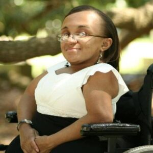 Vilissa Thompson is smiling and posing in her wheelchair. Vilissa has brown skin, wears glasses and has long straight hair.