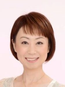 Noriko smiles for her headshot. She has olive skin and a short cropped haircut.