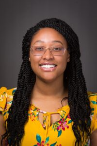 Charity smiles for her headshot. Charity has brown skin, wears transparent framed glasses and has styled her hair into long twists.