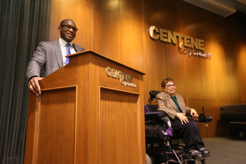 A man in a suit stands behind a podium speaking into a microphone. A woman using a wheelchair is beside him. The wall behind the stage says Centene Corporation.