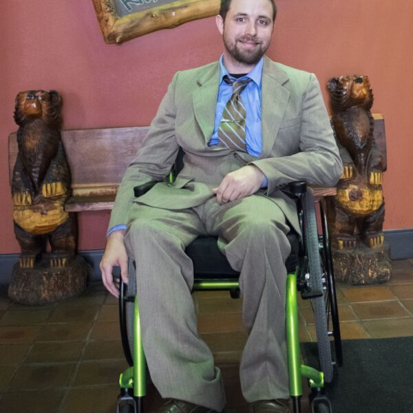 Bryan is seated in a lime green wheelchair. He is wearing a tan suit with a blue buttoned shirt and a brown tie.