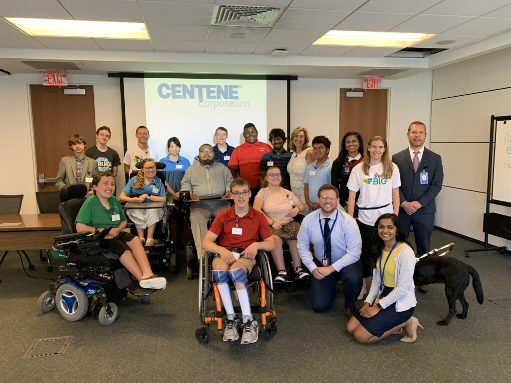 A group of about 20 people in a conference room smile at the camera. Some are adults in business suits, others are high school students. Five people in the group are using wheelchairs and there is one guide dog. A projector behind the people says Centene Corporation.