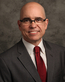 Michael Reese poses for a headshot. He is wearing black glasses, a grey suit and a red satin tie.