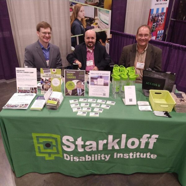 Jason, Brian and Scott sit behind the Starkloff event table. The table is covered in a green tablecloth and Starkloff swag is placed on top for attendees.