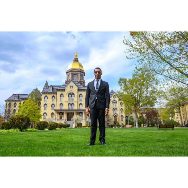 Justice is standing on grass in front of a domed cathedral. He is wearing a navy suit and has on grey sunglasses.
